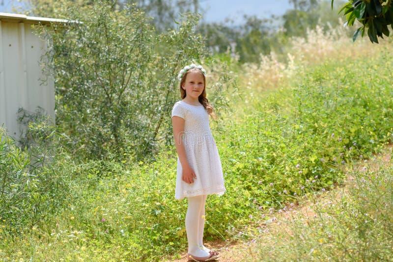 Mooi meisje met witte kleding die zich op een mooie weg bij de zonsondergang bevinden stock fotografie