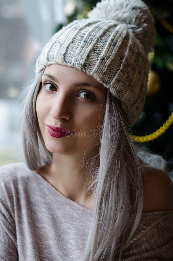 Mooi meisje met zilveren grijs haar in pom pom hoed met wijn rode lippen in de winter stock foto's