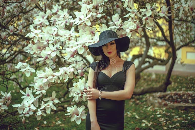 Mooi meisje met zwart haar in een zwarte kleding op een achtergrond van een magnoliabloem stock afbeeldingen