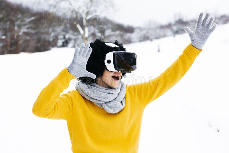 Mooi meisje met zwart haar en gele sweater met virtuele glazen openlucht in de sneeuw stock afbeelding