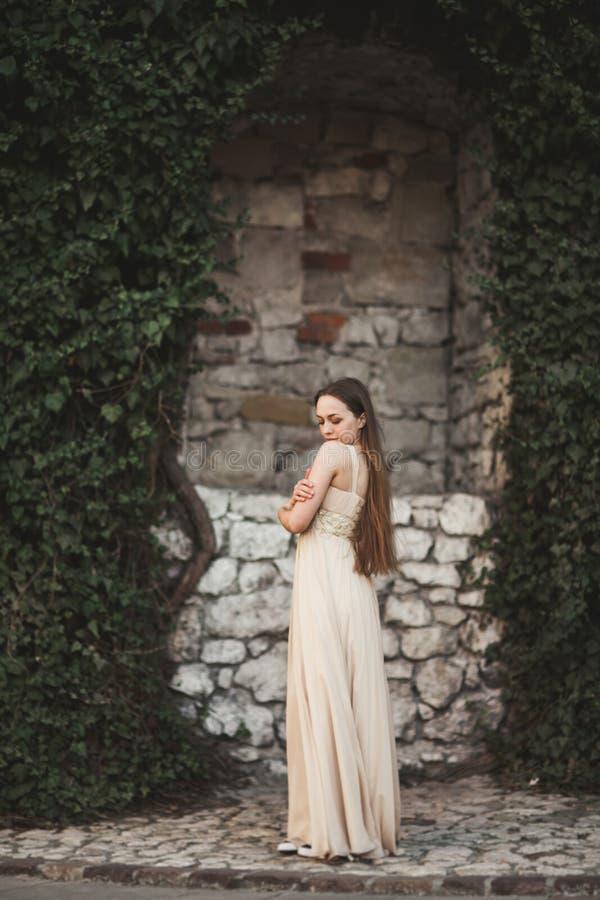 Mooi meisje, model dichtbij de muur van bladeren en struiken in park stock foto's