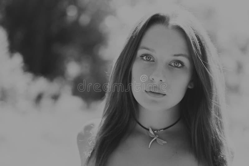 Mooi meisje onder bloemgebieden royalty-vrije stock afbeeldingen