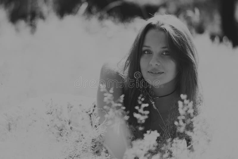Mooi meisje onder bloemgebieden stock afbeelding