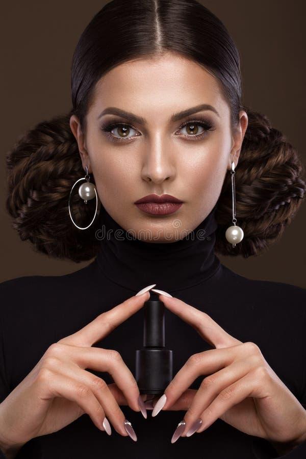 Mooi meisje, ongebruikelijk kapsel, heldere make-up, rode lippen en manicureontwerp met een kruik nagellak in haar handen royalty-vrije stock fotografie