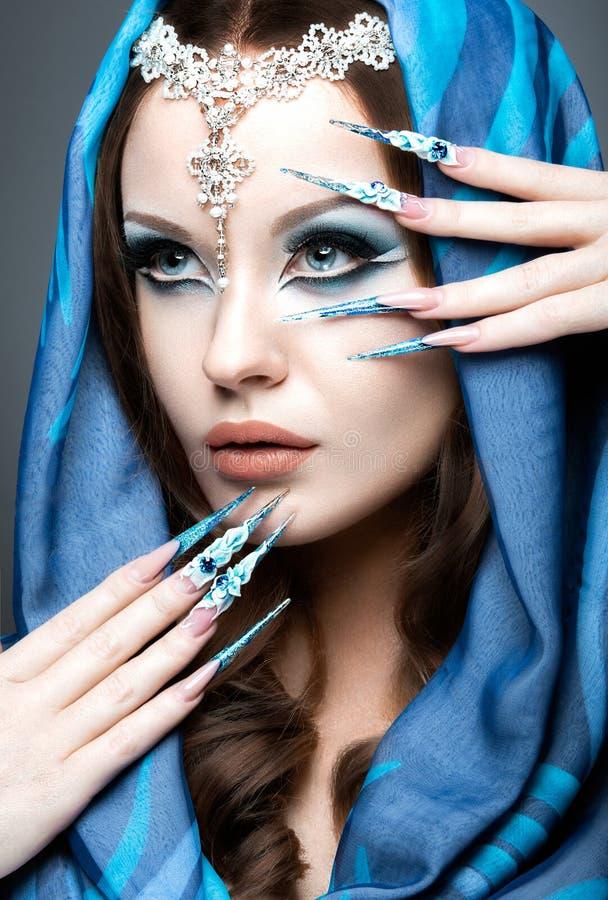 Mooi meisje in oostelijk Arabisch beeld met lange spijkers en heldere blauwe samenstelling royalty-vrije stock afbeeldingen