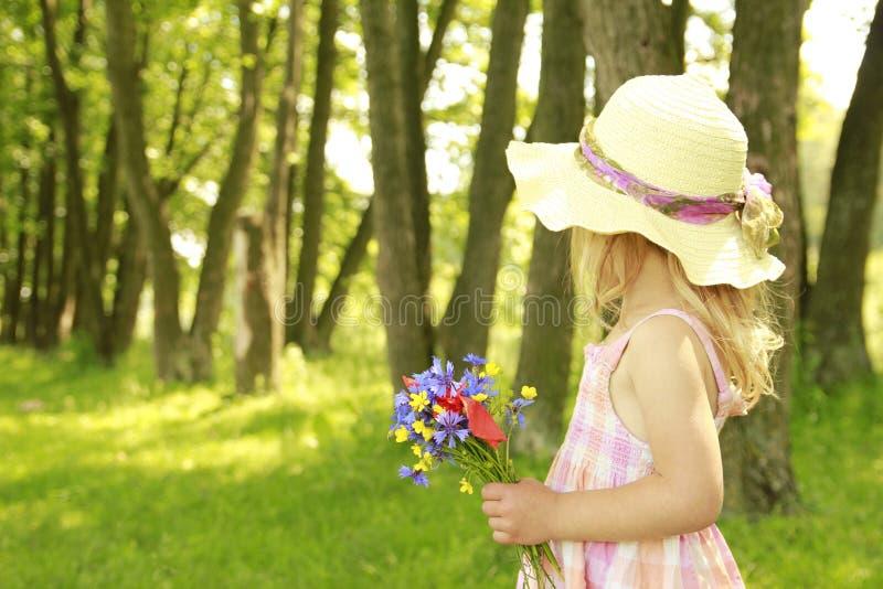 Mooi meisje op aard met een boeket van bloemen stock afbeeldingen