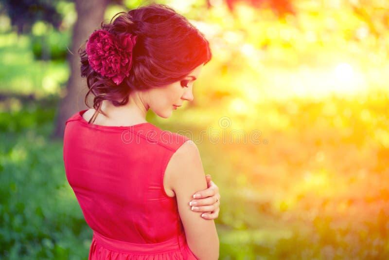 Mooi meisje op de aard in het park Tegen de achtergrond stock fotografie