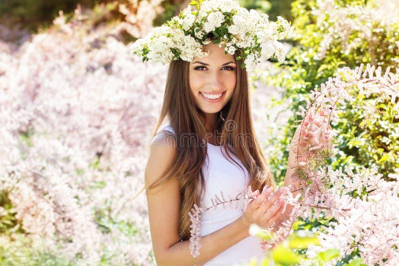 Mooi meisje op de aard in kroon van bloemen royalty-vrije stock afbeeldingen