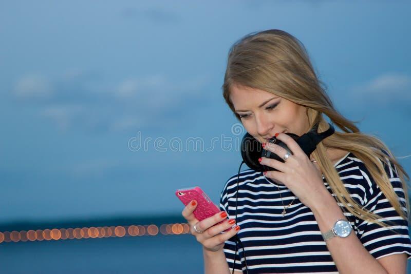 Mooi meisje op de achtergrond van de rivier na zonsondergang stock foto