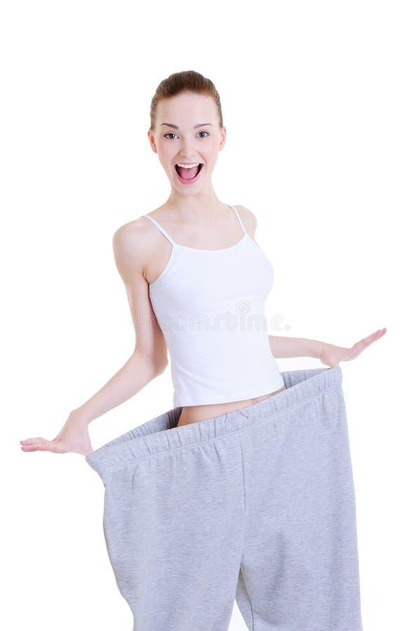 Mooi meisje op de grote broeken na dieet stock foto