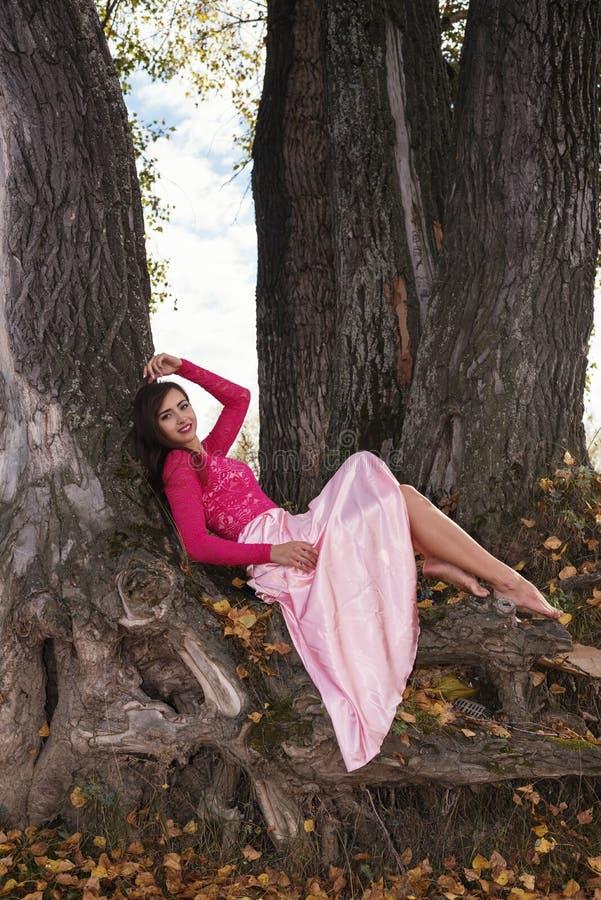 Mooi meisje op de wortels van de boom royalty-vrije stock foto