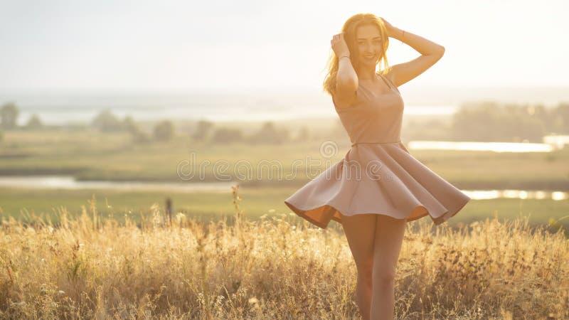 Mooi meisje op een gebied in een kleding bij zonsondergang, een jonge vrouw in een nevel van de zon die van aard genieten stock afbeeldingen
