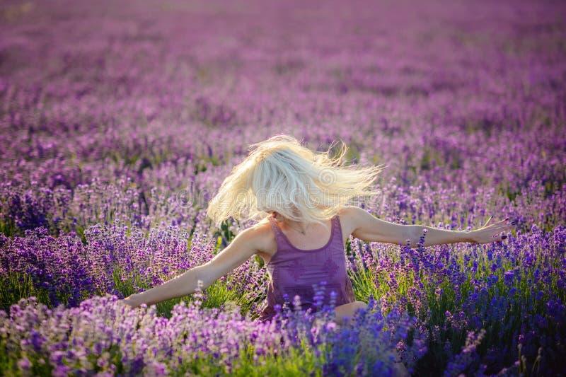 Mooi meisje op een gebied van lavendel op zonsondergang royalty-vrije stock foto's