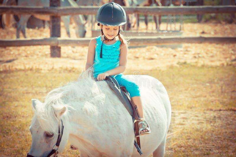 Mooi meisje op een paard Litllemeisje die een ho berijden royalty-vrije stock afbeeldingen