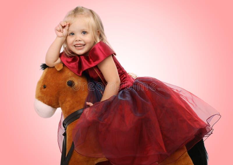Mooi meisje op een stuk speelgoed paard stock afbeeldingen