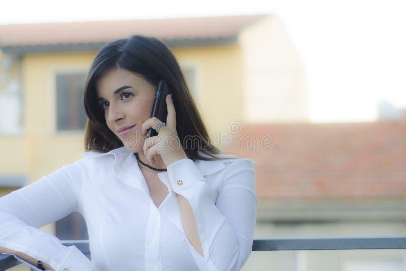 Mooi meisje op profiel op de telefoon openlucht stock fotografie