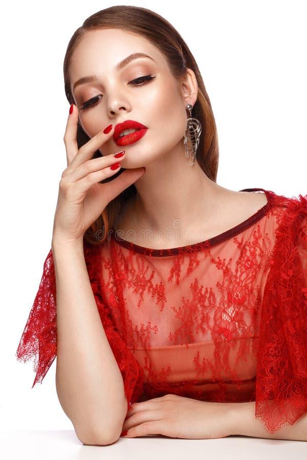 Mooi meisje in rode kleding met klassieke samenstelling en rode manicure Het Gezicht van de schoonheid royalty-vrije stock foto's