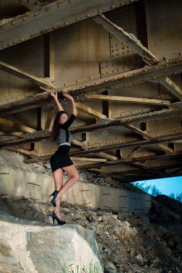 Mooi meisje in rok onder de brug stock afbeelding