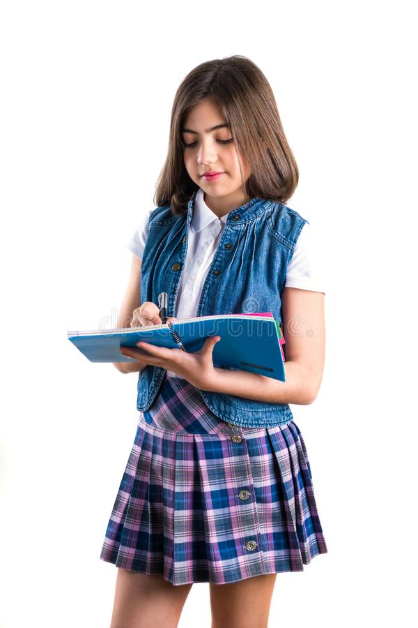 Mooi meisje in school eenvormig met een notitieboekje in haar hand  royalty-vrije stock afbeeldingen