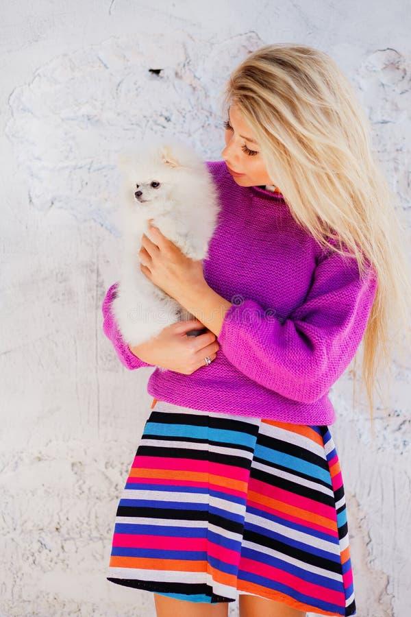 Mooi meisje, sexy vrouw met de lange greep van het blondehaar op het hand kleine leuke pomeranian spitz hond of puppyhuisdier royalty-vrije stock fotografie
