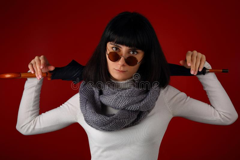 Mooi meisje in sjaal en retro glazen met paraplu stock fotografie