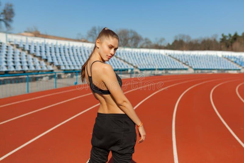 Mooi meisje in sportkleding die zich op de renbaan bevinden en voorbereidingen treffen te lopen Ochtendopwarming vóór oefening royalty-vrije stock foto