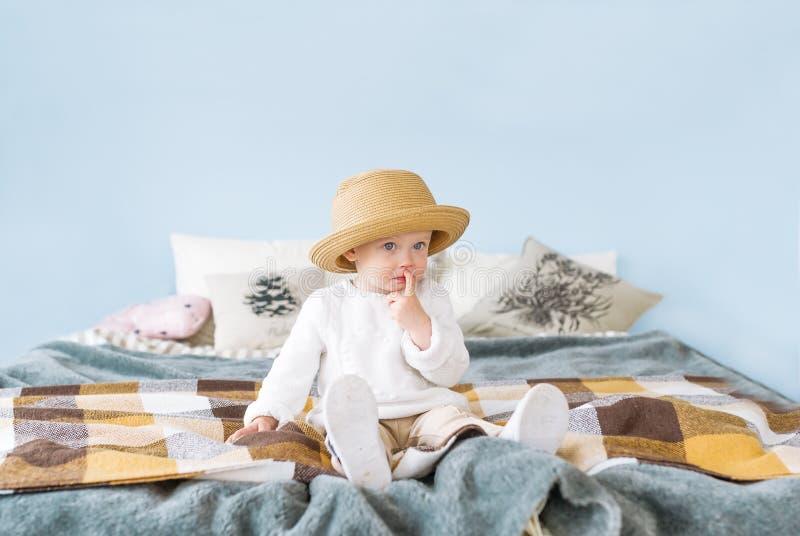 Mooi meisje in strohoed met blauwe ogen en een nadenkende uitdrukkingszitting op haar bed stock foto's