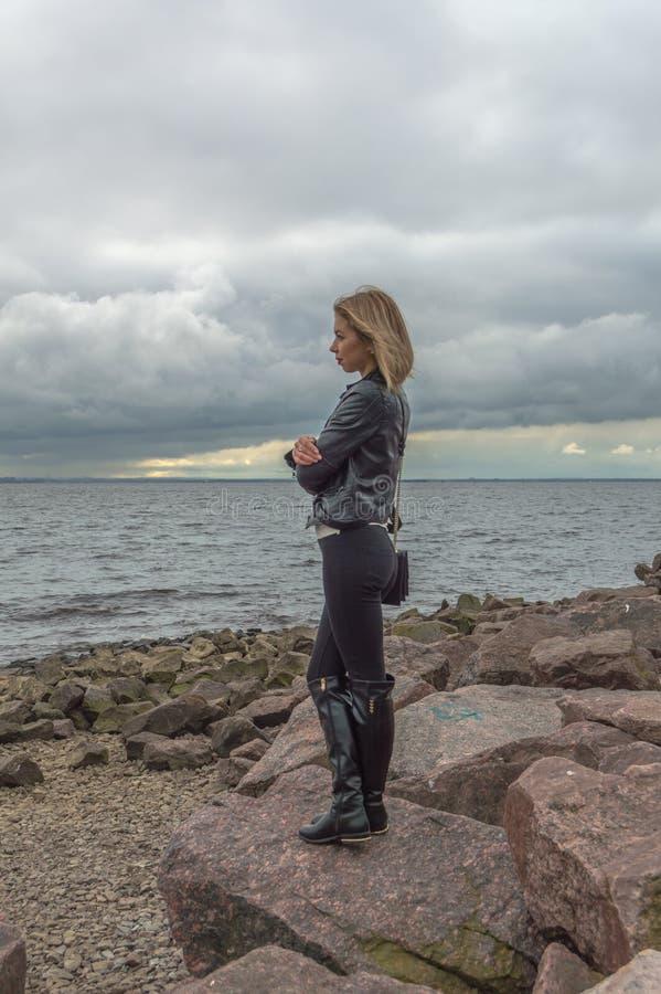 Mooi meisje tegen de hemel, tribunes op een rots royalty-vrije stock afbeelding