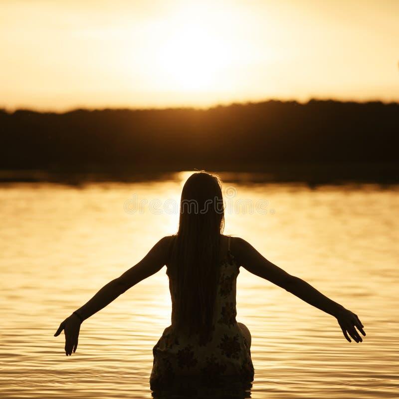 Mooi meisje in water op zonsondergang royalty-vrije stock afbeeldingen