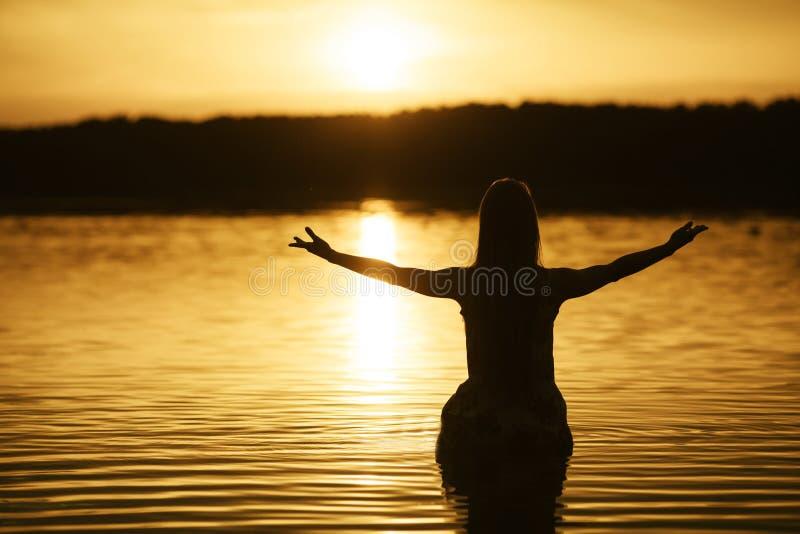 Mooi meisje in water op zonsondergang stock afbeeldingen