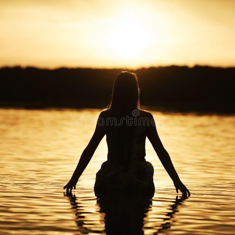 Mooi meisje in water op zonsondergang royalty-vrije stock afbeelding
