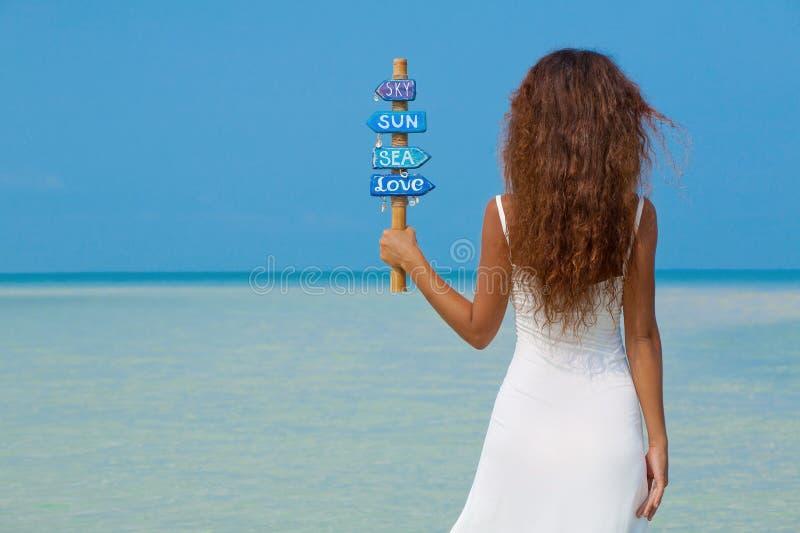 Mooi meisje in witte kleding op het strand stock foto
