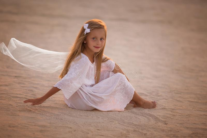 Mooi meisje in witte kledingszitting op het zand in de woestijn bij zonsondergang royalty-vrije stock foto's