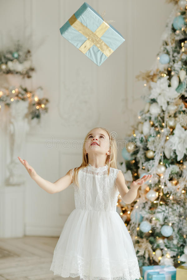Mooi meisje zich dichtbij de Kerstboom bevinden, en thro die stock afbeelding
