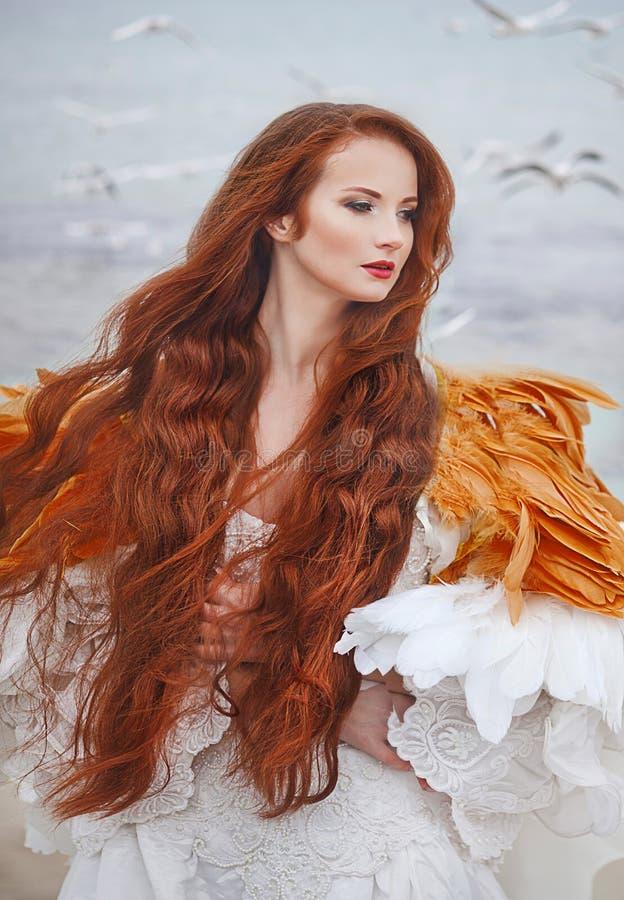 Mooi meisje zoals een zwaan op het strand stock afbeelding