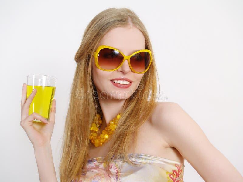 Mooi meisje in zonglazen met sap stock afbeelding