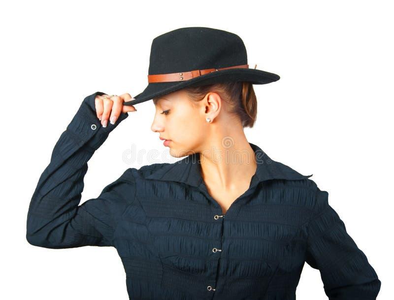 Mooi meisje in zwart overhemd en zwarte hoed stock afbeelding