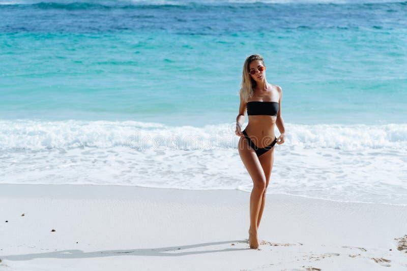 Mooi meisje in zwart zwempak en zonnebril die dichtbij oceaan op strand rusten stock foto's
