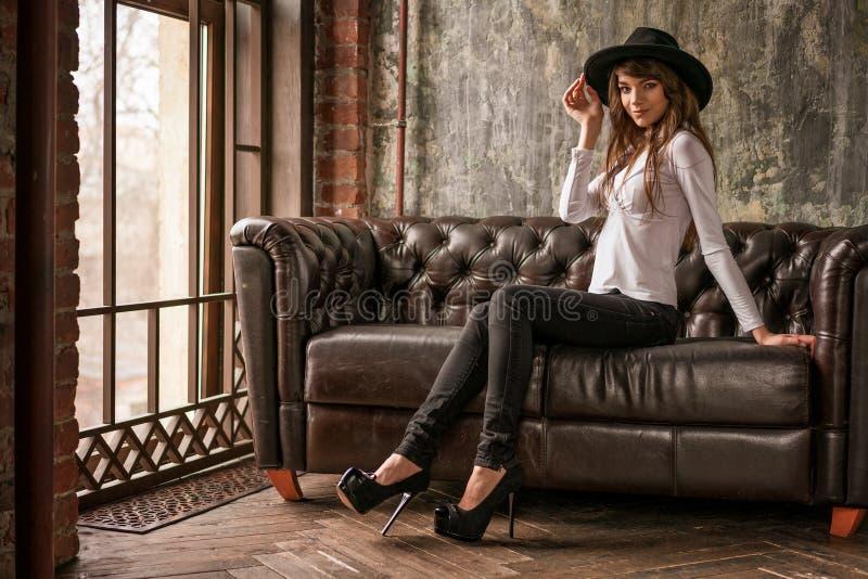 Mooi meisje in zwarte hoedenzitting op bank, modieuze vrouw stock afbeeldingen