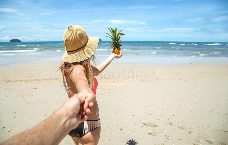 Mooi meisje in zwempak en ananasgangen op de strandgreep stock foto