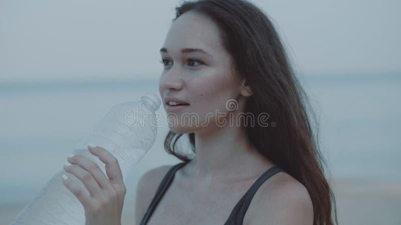 Mooi meisjes jogger drinkwater op het zandige strand stock fotografie