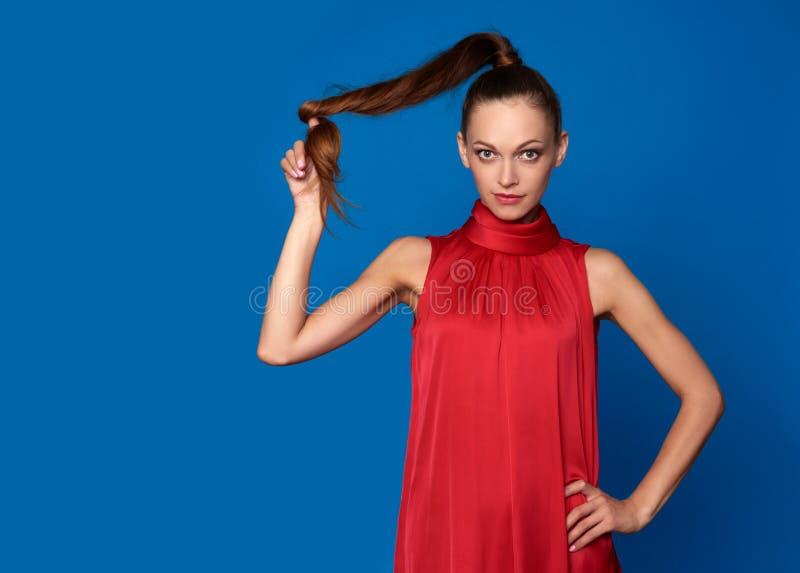 Mooi meisjes winh lang bruin haar over blauw royalty-vrije stock afbeelding
