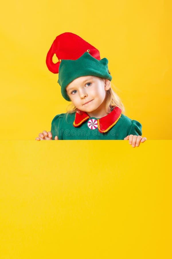 Mooi meisjeskind in elfkostuum Op een gele plaats als achtergrond voor tekst, exemplaarruimte stock foto