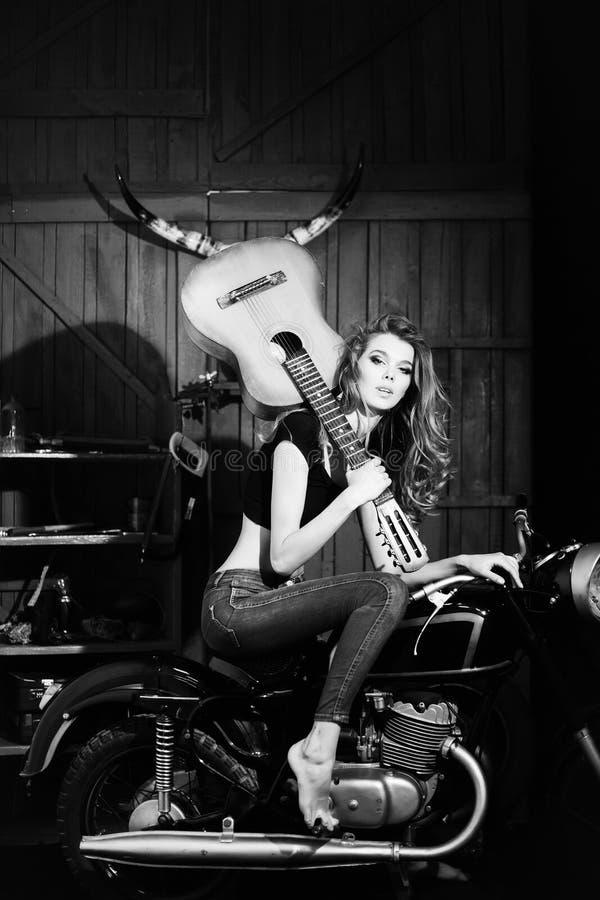 Mooi meisjesmodel met gitaarzitting op motorfiets royalty-vrije stock fotografie
