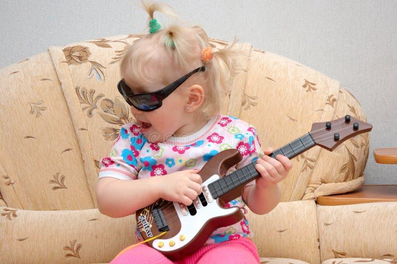 Mooi meisjespel op stuk speelgoed gitaar. stock afbeeldingen