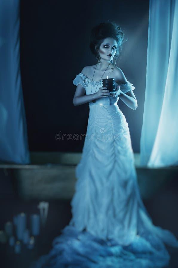 Mooi meisjesspook, heksenbruid in een witte kleding die een zwarte brandende kaars in handen houden stock fotografie