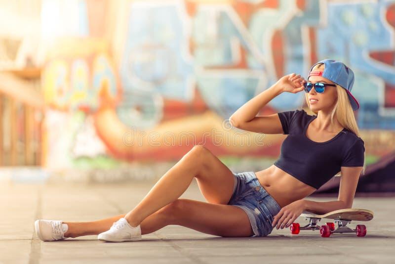 Mooi met een skateboard rijdend meisje royalty-vrije stock afbeelding