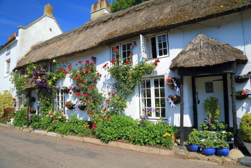 Mooi met stro bedekt plattelandshuisje met tuin stock afbeelding