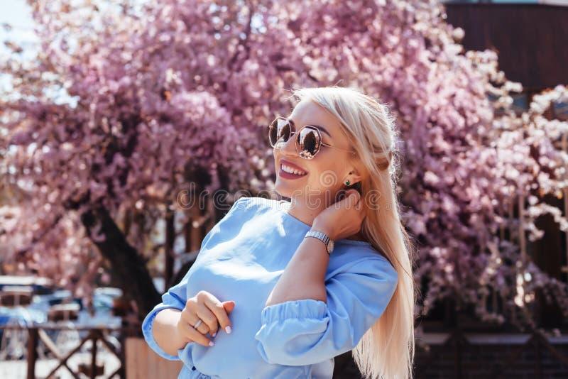 Mooi model in blauwe kleding door de lente bloeiende boom royalty-vrije stock foto's
