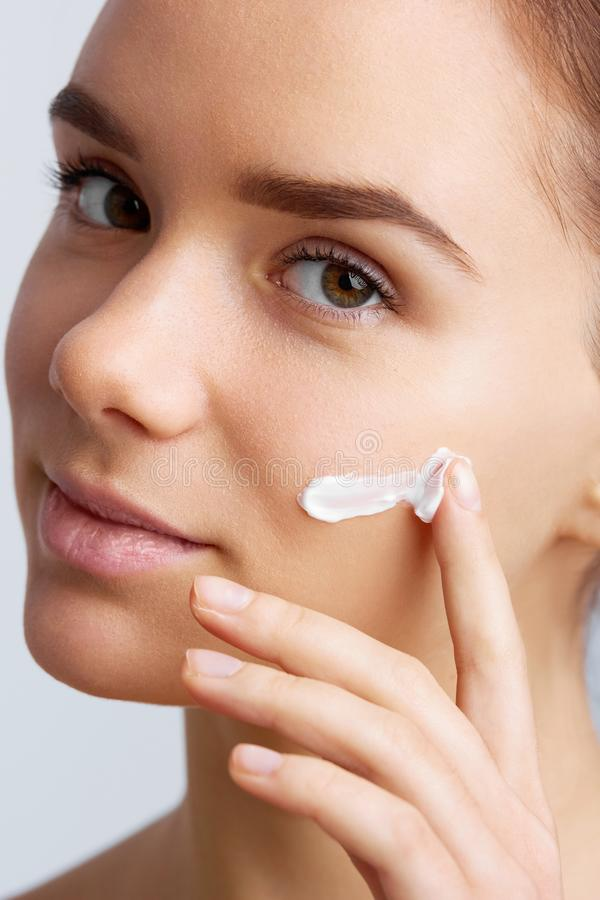 Mooi model die kosmetische roombehandeling op haar gezicht toepassen Bevochtigt het close-up jonge mooie gezicht van meisje het v royalty-vrije stock afbeeldingen